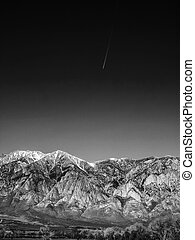 Black and white image of Snow capped mountains, blue sky,...