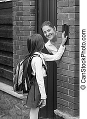 Black and white image of young mother opens door to her daughter after going to school