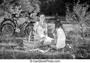 Black and white image of young woman relaxing with her daughter on picnic