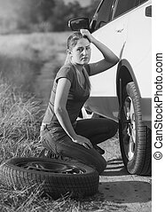 Black and white image of young woman sitting at car with flat tire and looking in camera