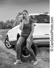 Black and white image of young woman sitting on car spare wheel and calling auto service in field