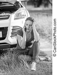 Black and white image of young woman sitting on ground and leaning on broken car
