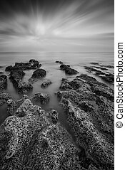 Black and white landscape looking out to sea with rocky...