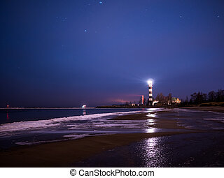 Black and white lighthouse at night in Baltic sea beach with stars