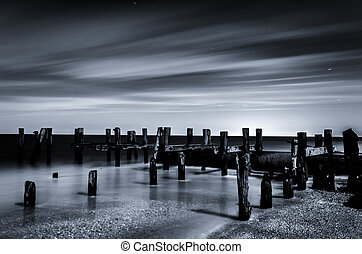 Black and white long exposure of pier pilings in the Delaware Bay at night, seen from Sunset Beach in Cape May, New Jersey.