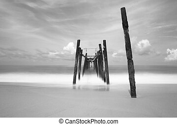 black and white of old bridge to the sea