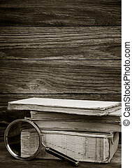 black and white photo. a pile of old books and magnifier on wooden background. the concept of the research, the study. with space for text