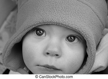 Closeup black and white photo of a baby with haunting eyes that pull you in.
