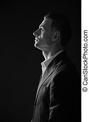 Black and white photo of a pensive man looking up