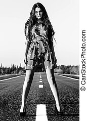 Black and white photo of a sexy woman staying on the road - ...