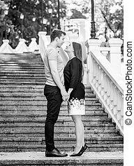 Black and white photo of couple in love holding hands on stairs