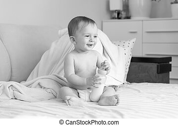 Black and white photo of cute smiling baby boy with bottle of milk sitting on bed