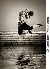 black and white photo of girl jumping on the roof in the water