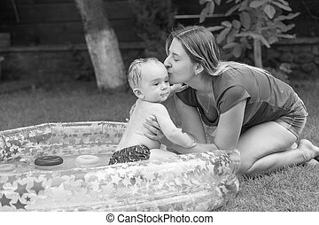 Black and white photo of happy young mother kissing her baby swimming in inflatable swimming pool