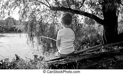 Black and white photo of little boy with wooden fishing rod ...