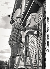 Black and white photo of man repairing air conditioner standing on ladder