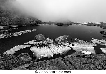 Black and white photo of pieces of ice in an alpine lake