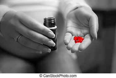 black and white photo of pregnant woman holding red pill on hand