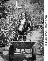 Black and white photo of teen girl posing with wheelbarrow at garden