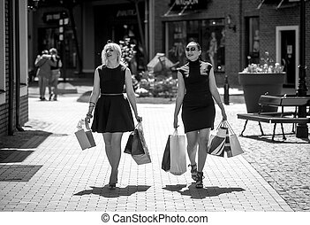 Black and white photo of two women walking with shopping bags