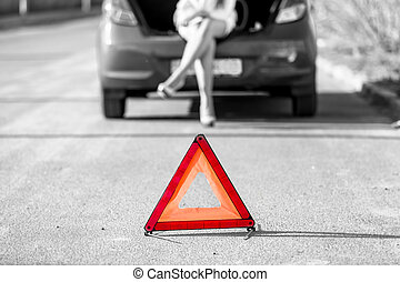 woman sitting on broken car near red warning sign