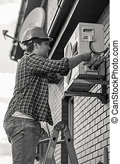 Black and white photo of young man repairing air conditioner