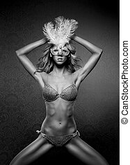 Black and white photo of young sexy woman in erotic lingerie and mask over the vintage background
