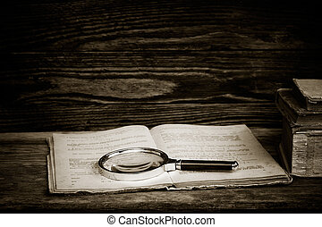 black and white photo. open old book with a magnifying glass and a stack of books on a wooden table. the concept of the study, the study. with space for text