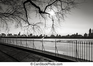 Black and White photograph of New York in winter. Urban view. Photo taken from the Reservoir in Central Park, NYC, with view of Manhattan skyline.