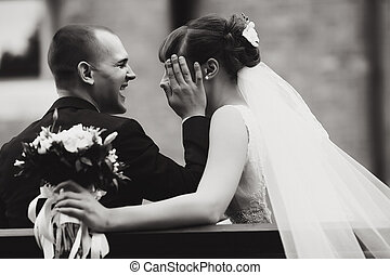 Black and white picture of a bride leaning to groom's hand sitting on the bench