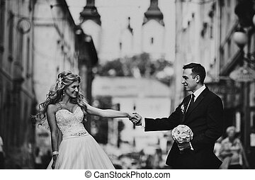 Black and white picture of a groom admiring bride on the old street