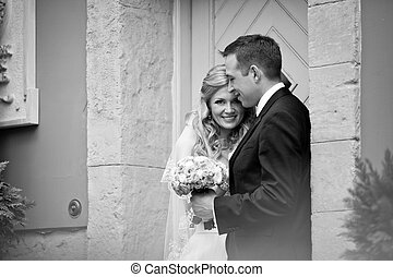 Black and white picture of the newlyweds standing at an old wooden door
