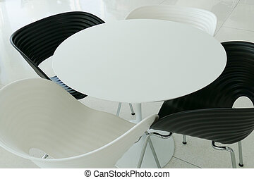 black and white plastic chair with white round desk