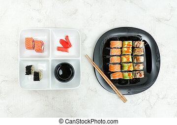 Black and white plate with various rolls and chopsticks. Top view