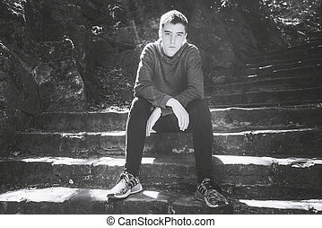 black and white portrait of a young man, sitting on stairs