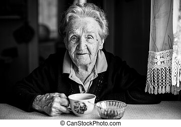 Black and white portrait of an elderly woman drinking tea looking at the camera.