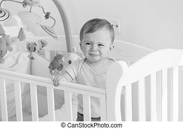 Black and white portrait of baby standing in crib and crying