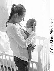 Black and white portrait of beautiful mother posing with her baby at child bedroom
