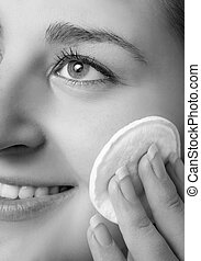 black and white portrait of beautiful woman removing makeup