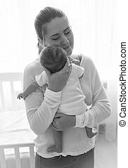 Black and white portrait of beautiful young mother posing with her baby