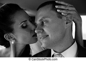 Black and white portrait of brunette bride kissing groom in chee
