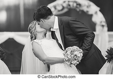 black and white portrait of groom and bride kissing at park...