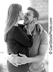 Black and white portrait of happy couple in love kissing at river