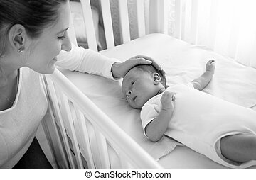 Black and white portrait of happy smiling mother caressing her baby lying in cot