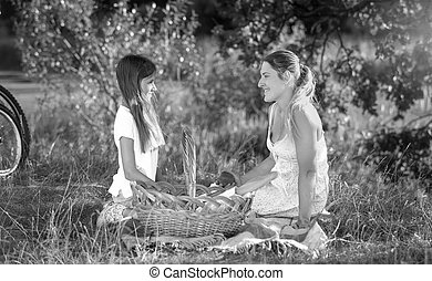 Black and white portrait of happy woman relaxing with her daughter on picnic