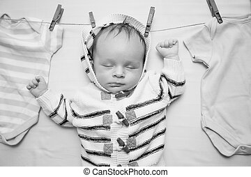 Black and white portrait of little baby boy hanging on clothesline