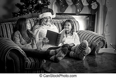 portrait of mother with two daughter reading book on sofa at fireplace