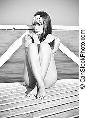 black and white portrait of sea mermaid enjoying summer: beauty model pretty girl having fun relaxing on sea pier on copy space background