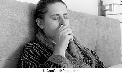 Black and white portrait of sick woman sitting in bed and using nasal spray