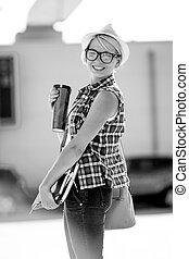 Black and white portrait of smiling stylish girl on street